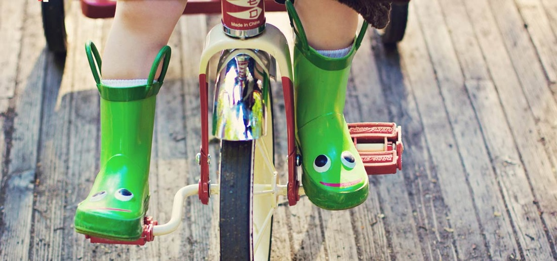 Child on tricycle with green boots
