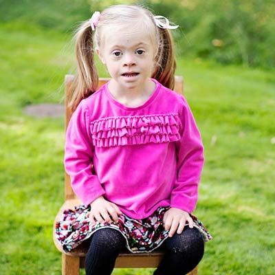 Girl in pink shirt sitting on chair